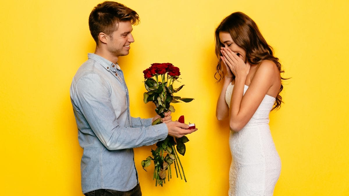 Man with engagement ring and roses making proposition of marriage his girlfriend