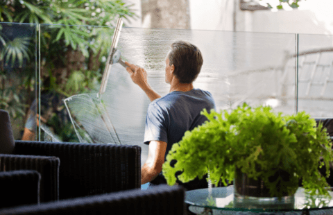 Image of a man cleaning a window from behind