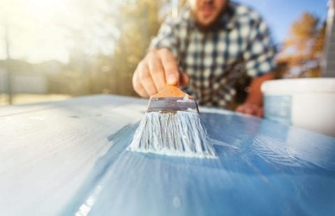 man painting a piece of wood with blue paint
